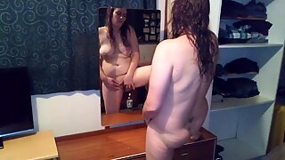 Woman standing in front of mirror masterbating